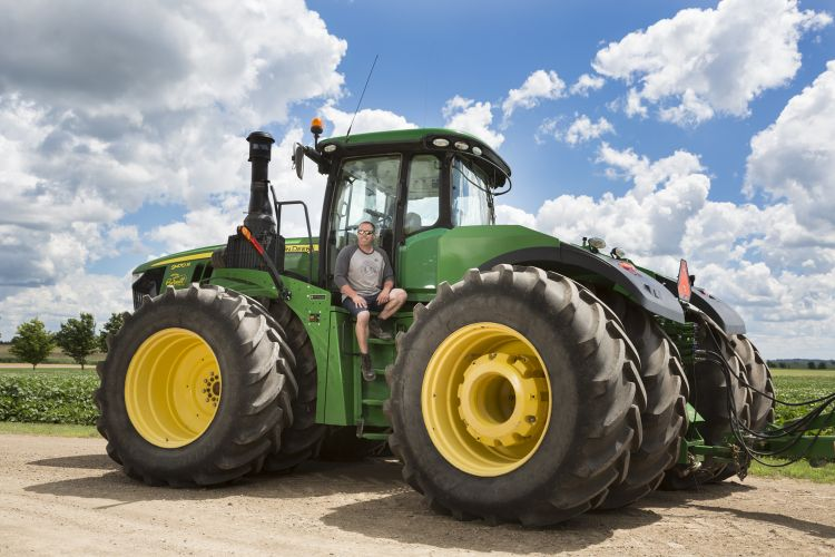man sitting on steps of a green tractor