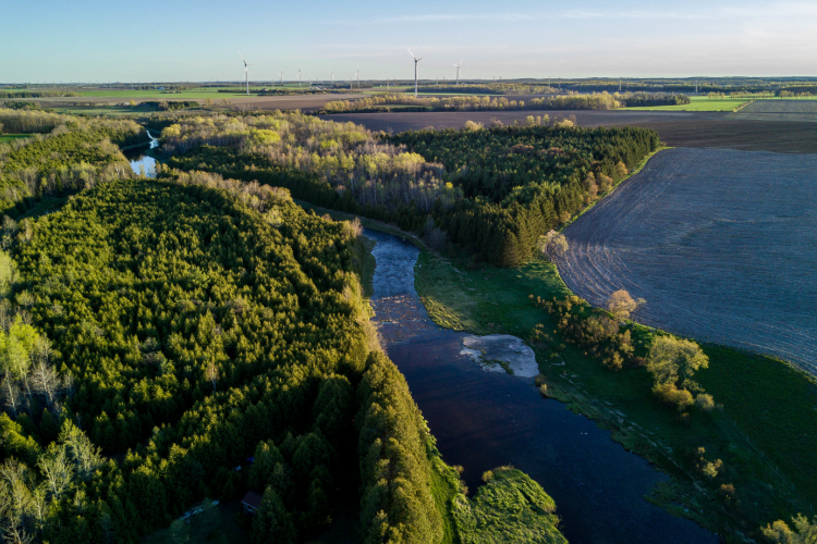 landscape image of river and farm field, wind turbines in distance