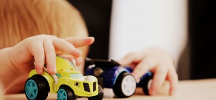 child's hands playing with cars